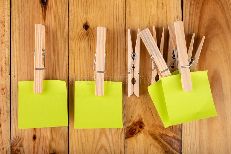 Kleurrijke kleverige die nota's op houten klemmen worden gehangen Kleverige nota's voor besparingsherinneringen op een houten lij stock foto's