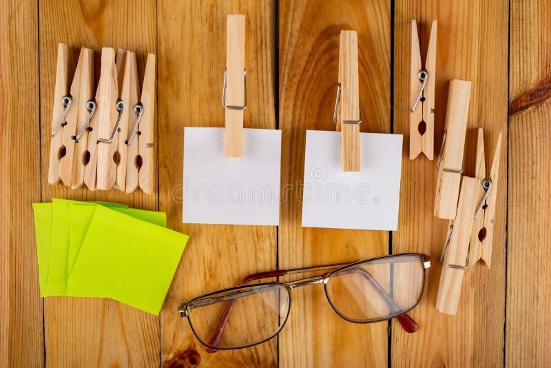 Kleurrijke kleverige die nota's op houten klemmen worden gehangen Kleverige nota's voor besparingsherinneringen op een houten lij stock foto