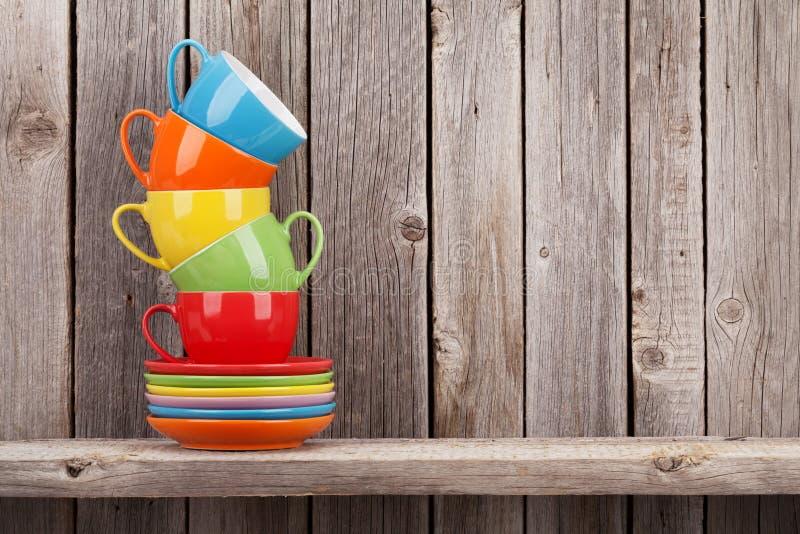 Kleurrijke koffiekoppen op plank royalty-vrije stock fotografie