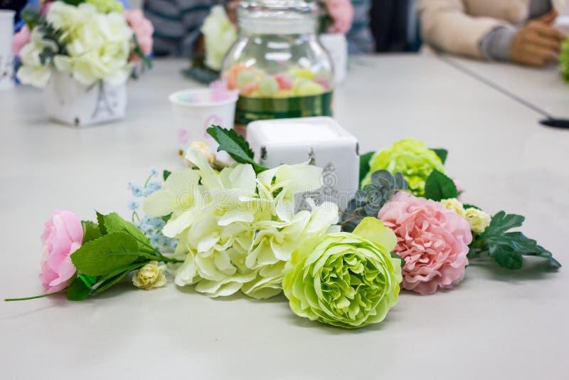 Kleurrijke kunstbloem op lijst, bloemstukworkshop stock afbeeldingen