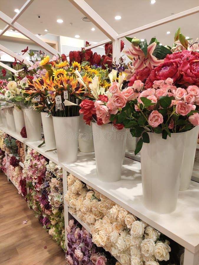 Kleurrijke kunstbloemen die van plastic vertoning in winkels voor verkoop worden gemaakt stock fotografie