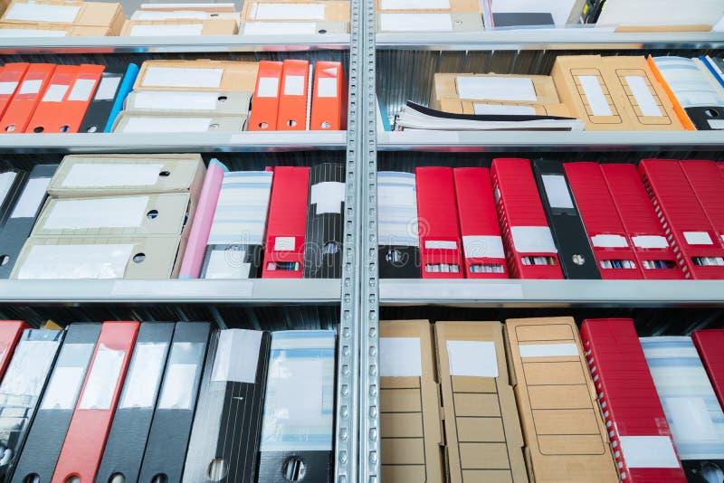 Kleurrijke lege blinde omslagen met dossiers in de plank Archivistisch, stapels documenten op het kantoor of de bibliotheek Fysie stock afbeelding
