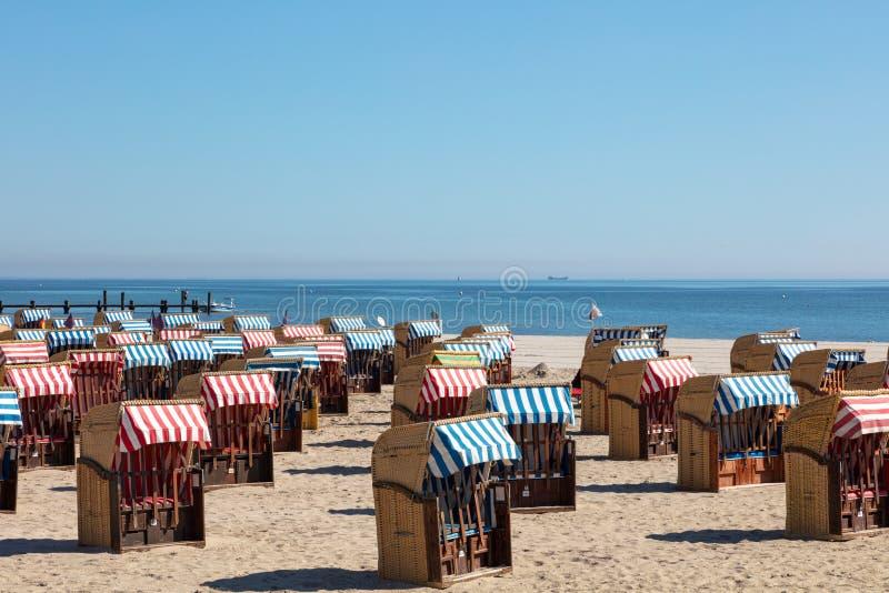 Kleurrijke ligstoelen op het strand in mooi weer stock afbeelding