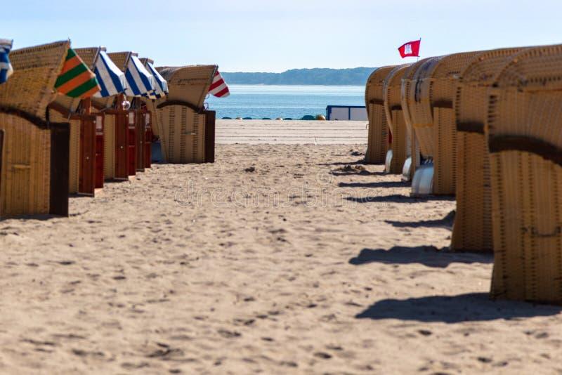 Kleurrijke ligstoelen op het strand in mooi weer stock fotografie