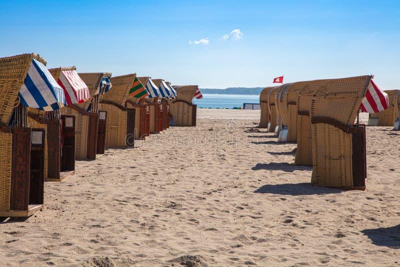 Kleurrijke ligstoelen op het strand in mooi weer stock afbeeldingen