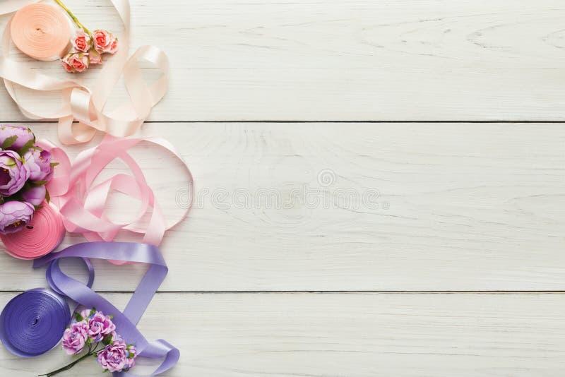 Kleurrijke linten en kouseband op houten lijst, de achtergrond van huwelijksvoorbereidingen stock afbeelding