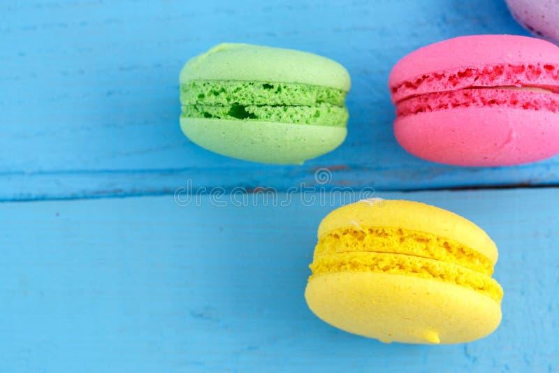 Kleurrijke macaroni of makaronskoekjes op blauwe houten uitstekende achtergrond Hoogste mening stock afbeeldingen