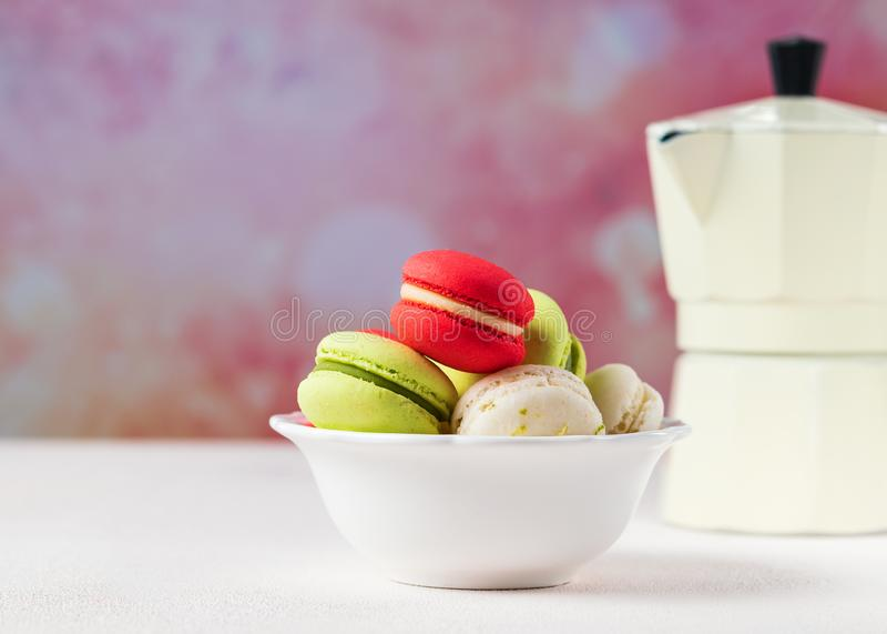 Kleurrijke macaronskoekjes in witte kom op pastelkleurachtergrond, exemplaarruimte royalty-vrije stock foto