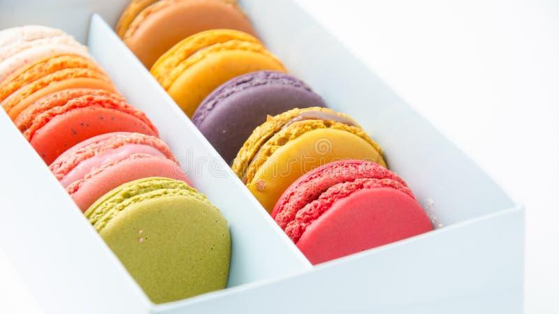 Kleurrijke makarons in de doos op witte achtergrond stock foto
