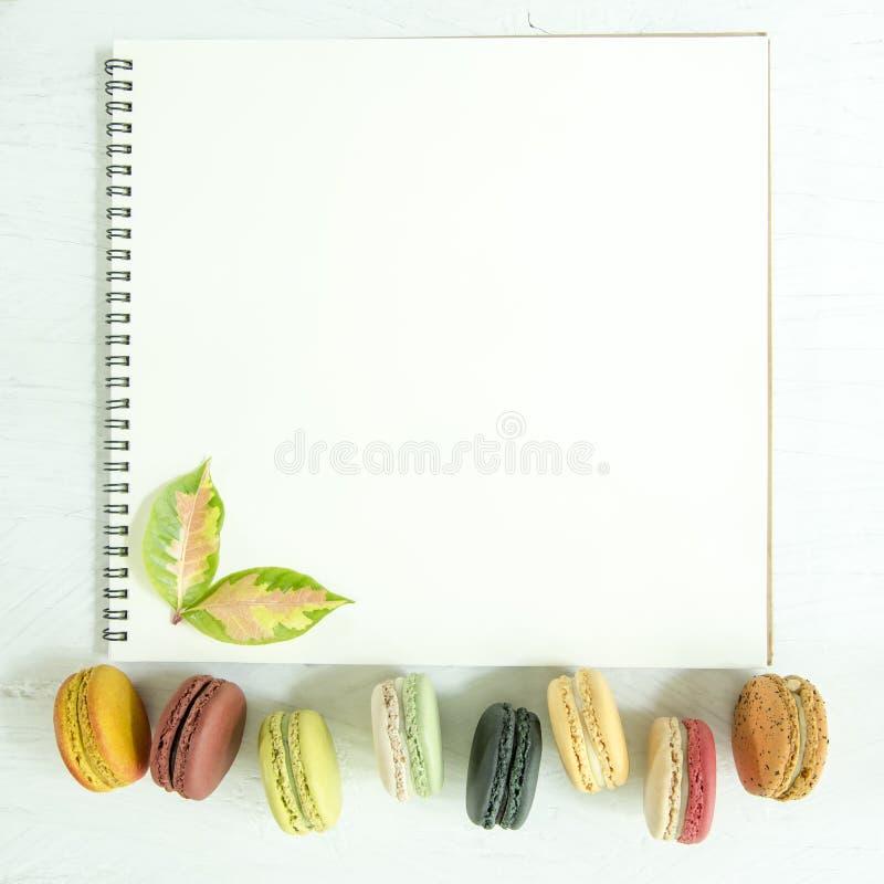 Kleurrijke makarons en bladeren met lege pagina van open witte nota stock afbeeldingen