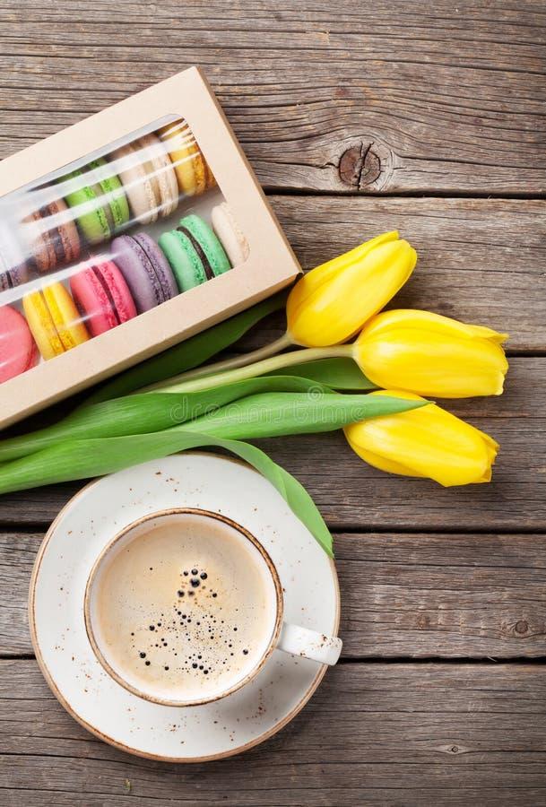 Kleurrijke makarons, koffiekop en gele tulpen royalty-vrije stock afbeeldingen