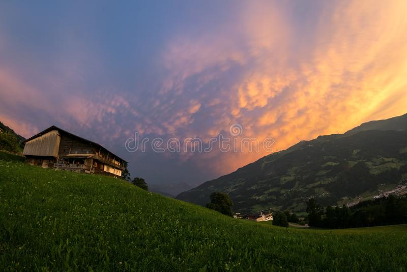 Kleurrijke mammatuswolken van een onweersbui over de Europese Alpen bij zonsondergang stock afbeelding