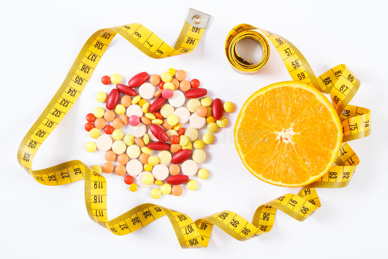 Kleurrijke medische pillen, verse sinaasappel en centimeter op witte achtergrond, gezondheidszorg, gezond levensstijl en vermager stock foto