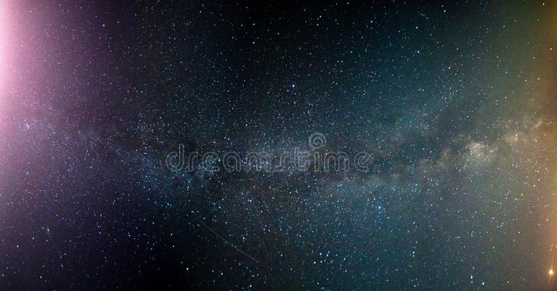 Kleurrijke Melkweg en geel licht Sterrige hemel met heuvels bij de zomer Mooi Heelal Nachthemel met veel Sterren stock foto