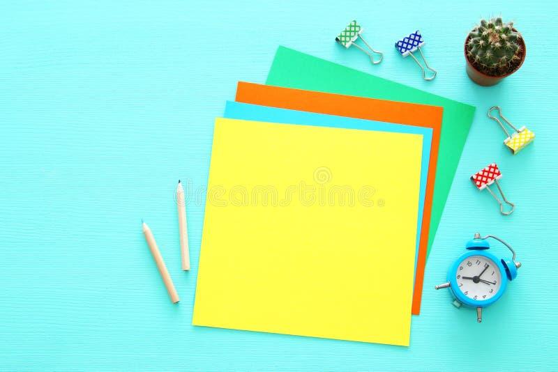 Kleurrijke memorandum lege pagina's en andere bureaulevering over lijst van het munt de blauwe bureau Hoogste mening stock fotografie