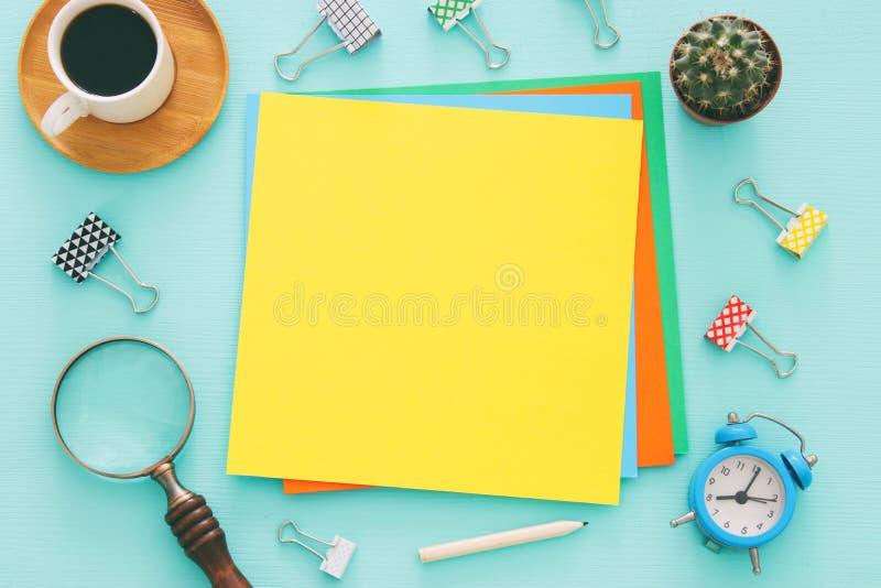 Kleurrijke memorandum lege pagina's en andere bureaulevering over lijst van het munt de blauwe bureau Hoogste mening stock afbeeldingen