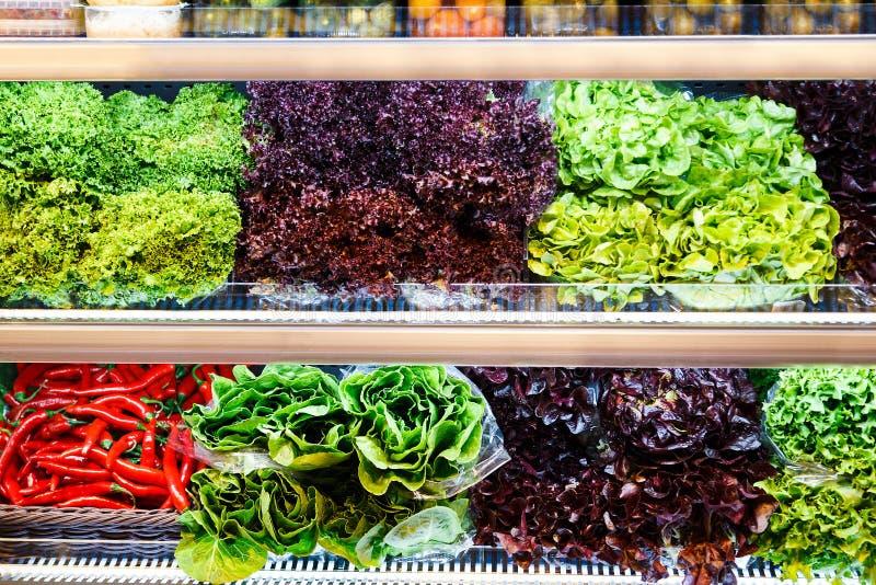 Kleurrijke mengeling van verschillende rode, groene, violette verse groenten en greens bij shelfs van supermarkt stock foto's
