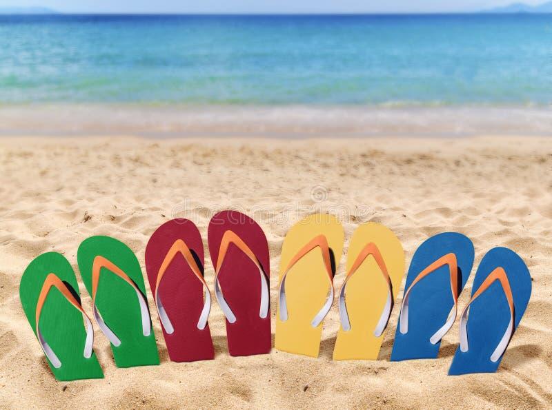 Kleurrijke Mensenlevensstijl vier ontspant wipschakelaars in het zand met overzees royalty-vrije stock fotografie
