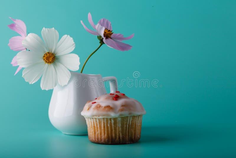 Kleurrijke muffin met bloem De achtergrond van de Aquakleur stock afbeeldingen