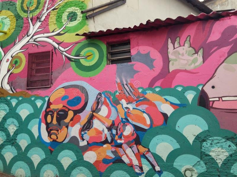 Kleurrijke muurschildering van straatkunst over een abstract water en boombeeldverhaal stock afbeelding