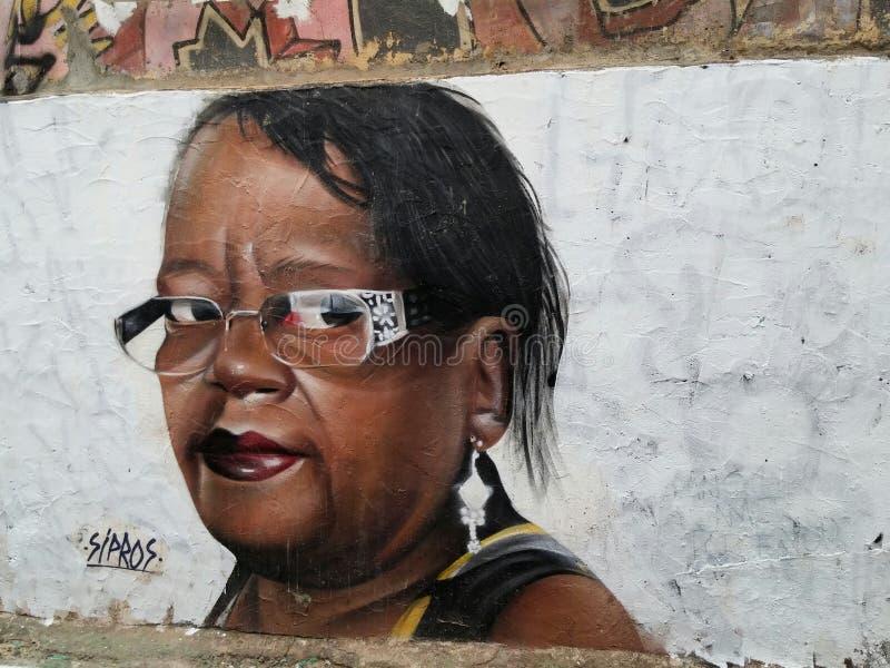 Kleurrijke muurschildering van straatkunst over een overweldigende Afrikaanse Amerikaanse vrouw stock fotografie