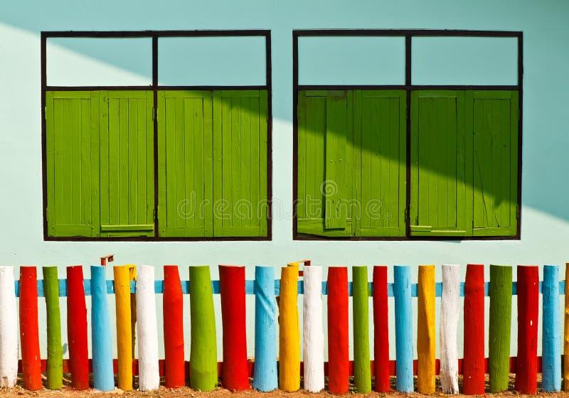 Kleurrijke omheining en groen venster stock afbeelding