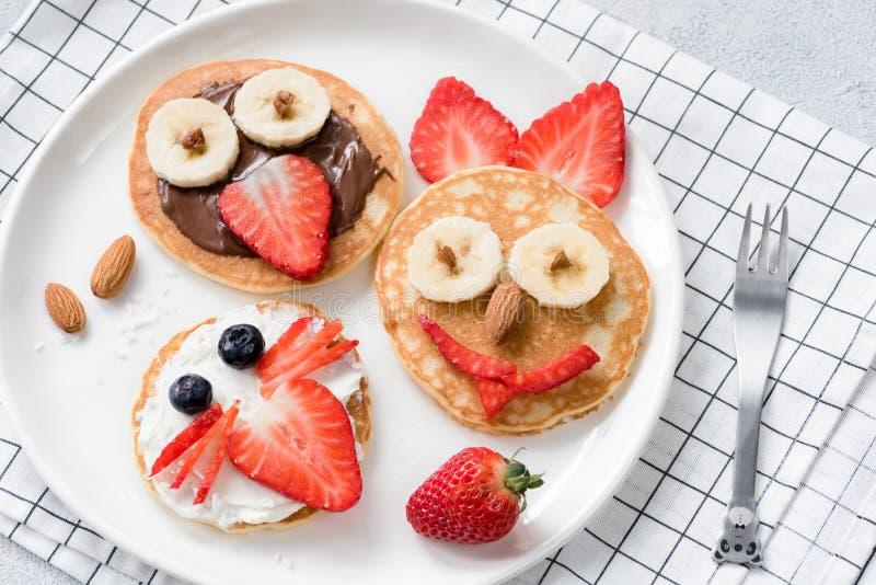 Kleurrijke ontbijtmaaltijd voor jonge geitjes De kunst van het pannekoekvoedsel, grappige dierlijke gezichten maakte met uitgespr royalty-vrije stock fotografie