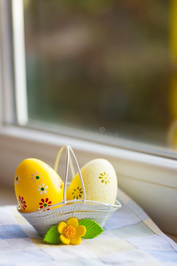 Kleurrijke oranje en gele paaseieren in mand met decoratieve bloem dichtbij venster in daglicht stock foto's
