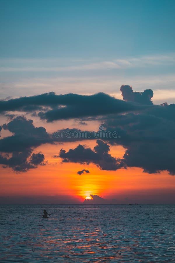 Kleurrijke oranje zonsondergang en oceaangolf en bewolkte hemel in mooie de zomerdag zonsondergangbeeld dat met weinig korrel en  royalty-vrije stock foto