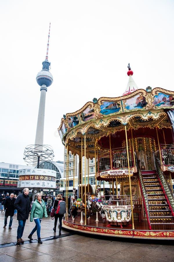 Kleurrijke oude die maniercarrousel in Alexanderplatz op de stadscentrum van Berlijn wordt gevestigd op een koud eind van de wint stock fotografie