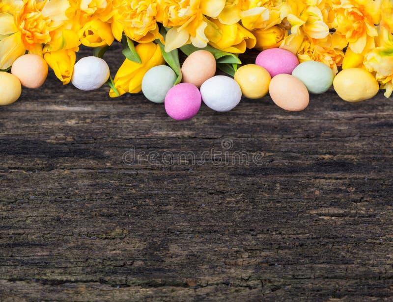 Kleurrijke paaseieren en gele narcissen en tulpen op hout royalty-vrije stock foto's
