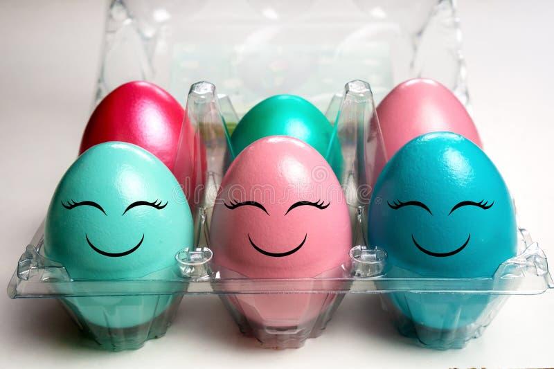 Kleurrijke paaseieren in het plastic pak van het eigeval met gelukkige emojigezichten stock afbeelding