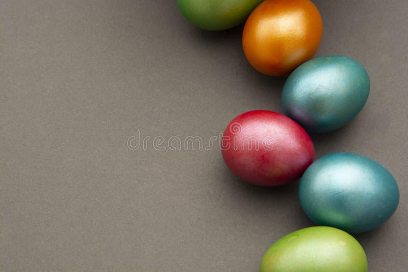 Kleurrijke paaseieren op grijze achtergrond met exemplaarruimte voor tekst, begroetende Pasen-Webkaart stock afbeelding
