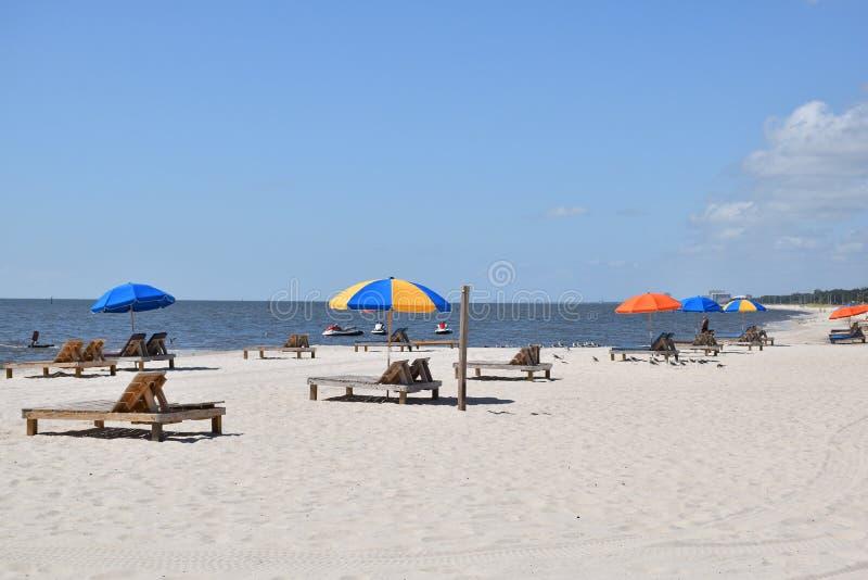 Kleurrijke paraplu's bij strand onder een blauwe hemel stock afbeelding