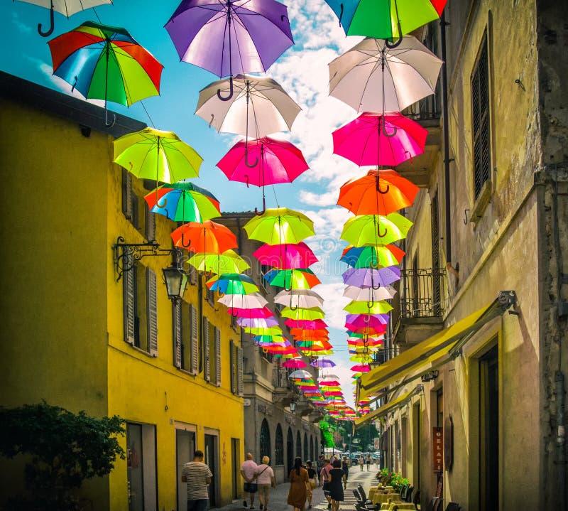 Kleurrijke paraplu's boven een voetstraat in Italië stock afbeelding