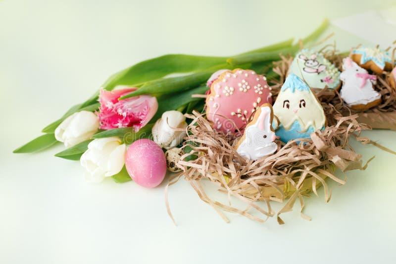 Kleurrijke Pasen-koekjes met het berijpen van suikerglazuurdecor, geschilderde kleurrijke eieren en tulpen op lichte lijst Het co royalty-vrije stock afbeeldingen