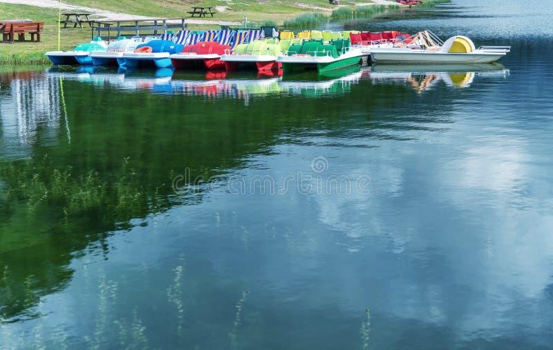 Kleurrijke pedalos op een bergmeer met bezinningen stock foto