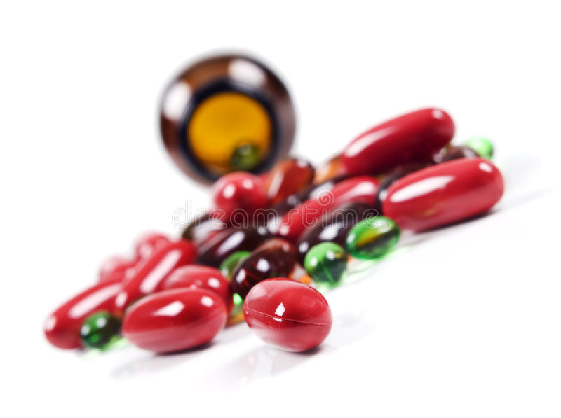 Kleurrijke pillen die voor een pillenfles worden uitgespreid. royalty-vrije stock foto's
