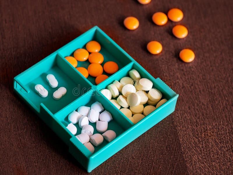 Kleurrijke pillen in een geneeskundedoos stock afbeelding