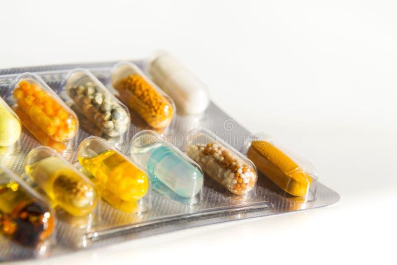 Kleurrijke pillen in transparante die geneeskundecapsule op witte achtergrond, de geneeskundeconcept wordt geïsoleerd van de ziek stock foto's