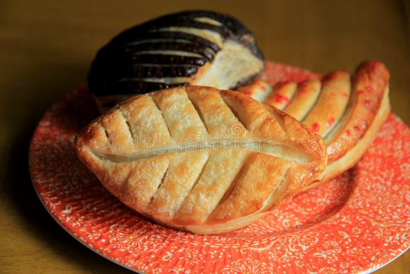 Kleurrijke plaat met drie buitensporige gebakjes stock afbeeldingen