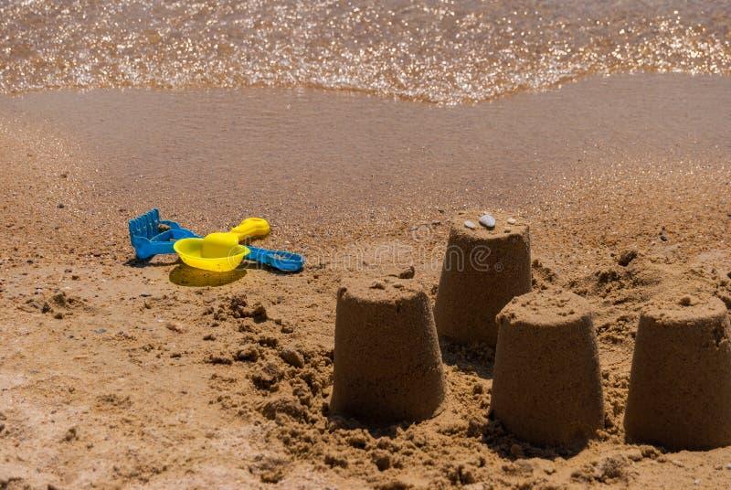 Kleurrijke plastic stuk speelgoed schop en hark in het zand op het strand door het overzees royalty-vrije stock afbeelding