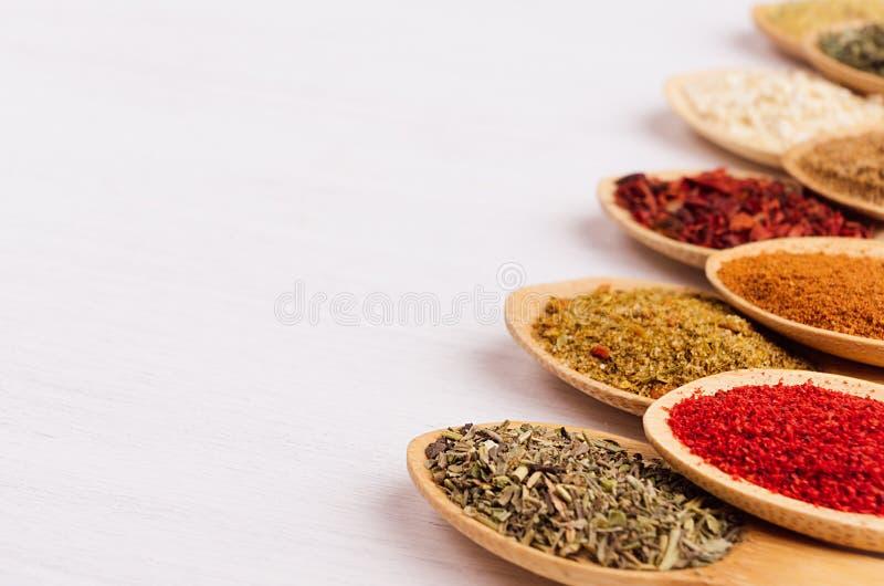 Kleurrijke poederkruiden op witte houten raad met exemplaarruimte, close-up, textuur royalty-vrije stock foto's