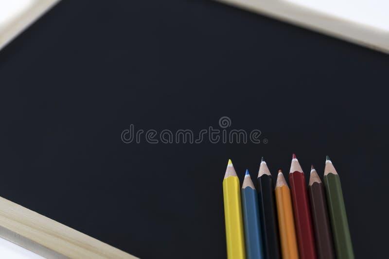 Kleurrijke potloden en zwarte raad stock foto's