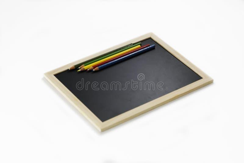 Kleurrijke potloden en zwarte raad royalty-vrije stock afbeeldingen