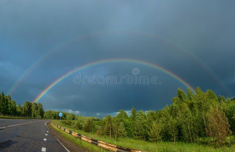 Kleurrijke regenboog over de weg stock foto's