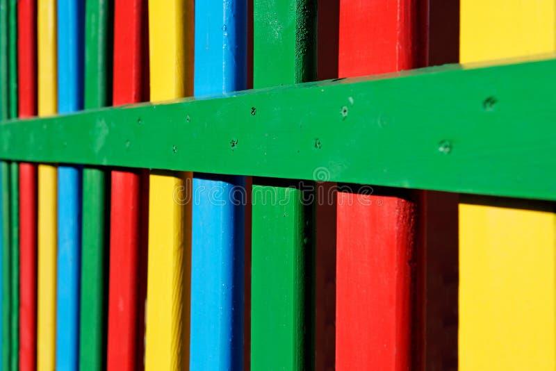 Kleurrijke rijen van geschilderd hout op een speelplaatsomheining royalty-vrije stock foto