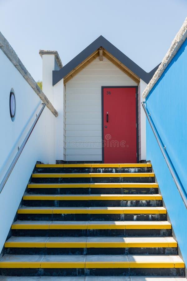 Kleurrijke rode deur, met elke één die, witte strandhuizen individueel worden genummerd op een zonnige dag, een mening die omhoog stock fotografie