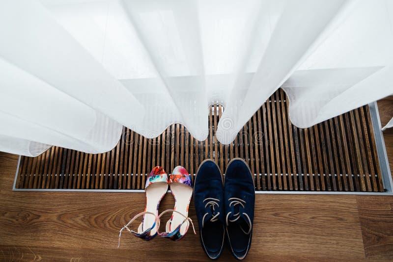 Kleurrijke sandals van de bruid en de blauwe schoenen van de bruidegom onder gordijn bij het venster royalty-vrije stock afbeelding