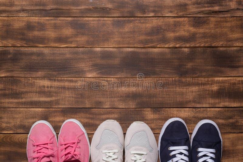 Kleurrijke schoenen hoogste mening Reeks verschillende tennisschoenen op houten vloer, exemplaarruimte royalty-vrije stock fotografie
